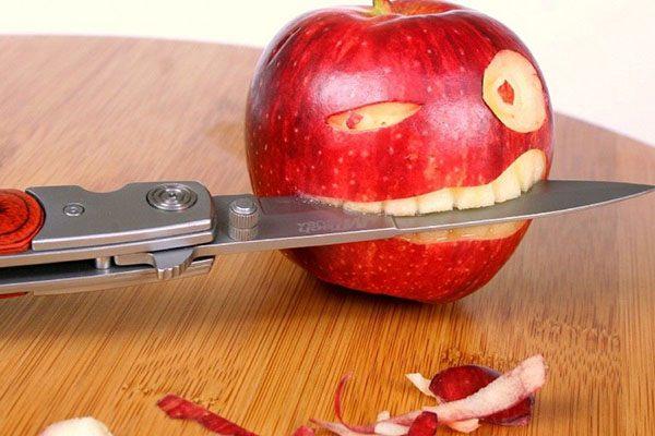 Нож вставлен в яблоко, как в будто в зубы человека