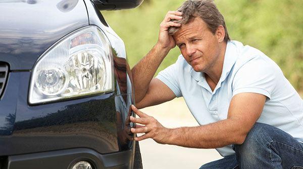 Мужчина сидит рядом с автомомбилем
