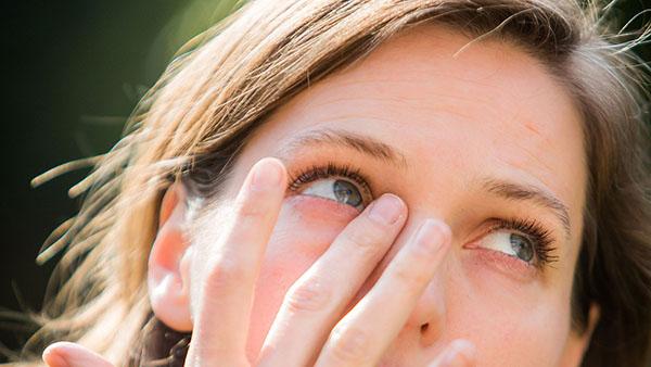 Девушка трет правый глаз