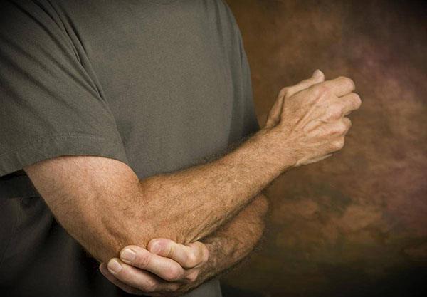 Мужчина трогает локоть на правой руке