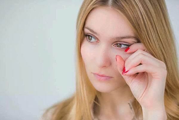 Девушка трет левый глаз