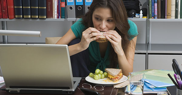 Девушка ест за компьютером