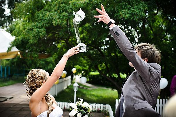 Молодожены бьют бокалы на свадьбе