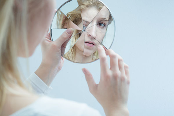 Девушка смотрит в треснутое зеркало