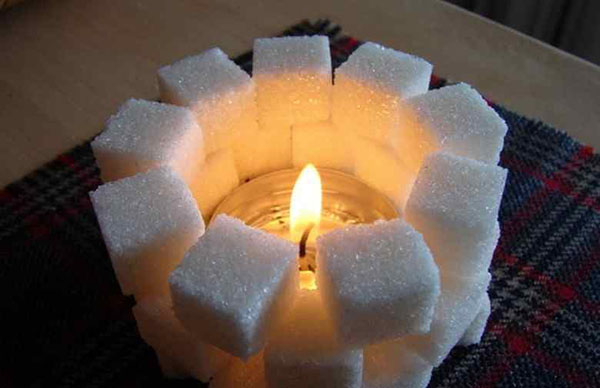 Свечка, окруженная кусочками сахара