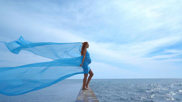 Беременная девушка у океана
