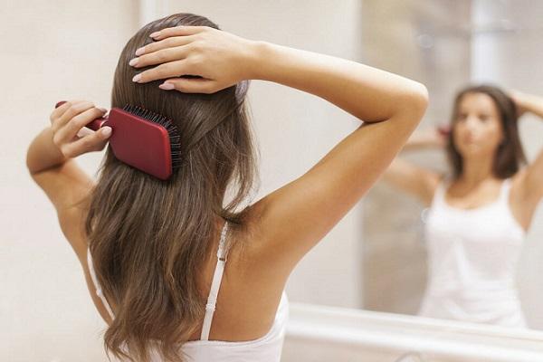 Женщина перед зеркалом расчесывает волосы