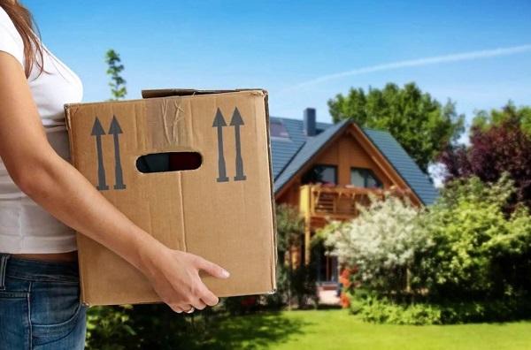 Женщина с коробкой на фоне дома