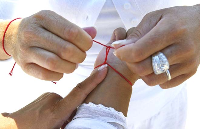 Процесс завязывания алой ленты-оберега на правое запястье